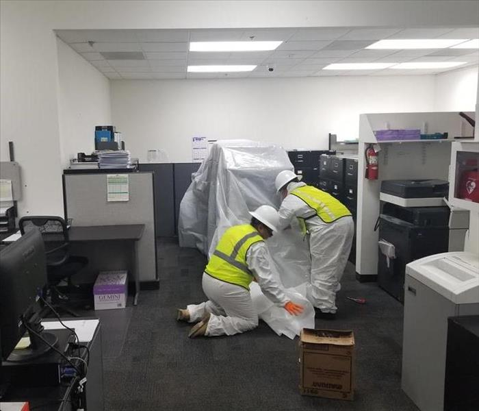 workers covering office furniture